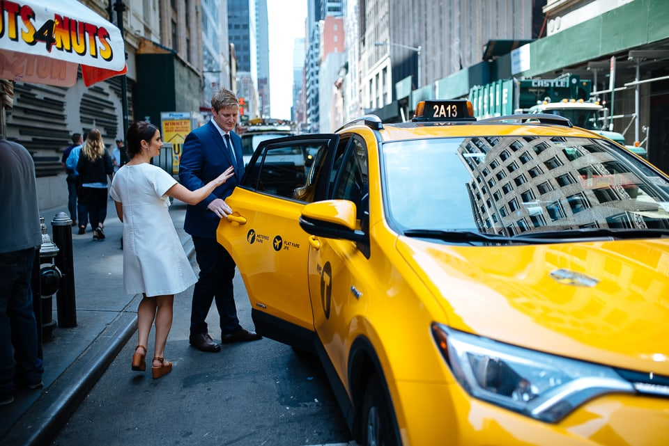 Bride and groom entering a cab