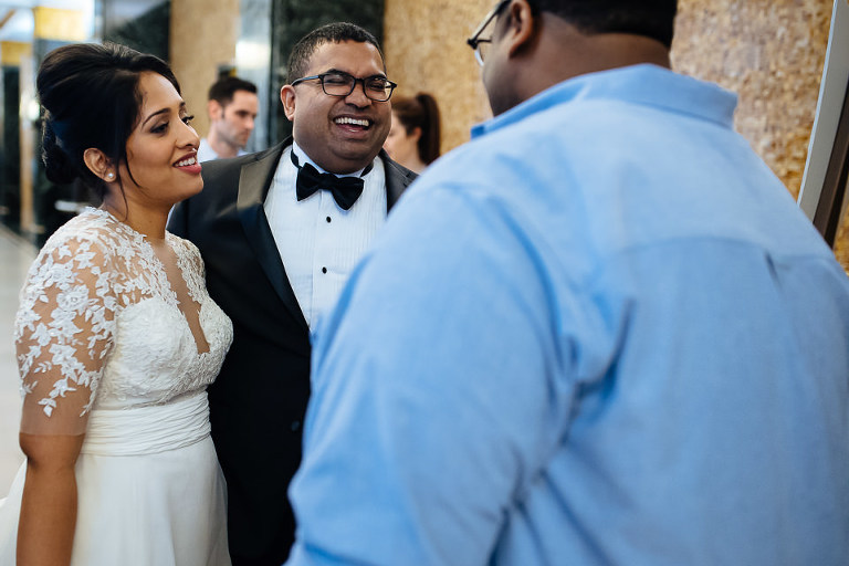 Bride and groom laughing with guest