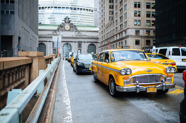 Vintage Checker cab taking bride and groom to their ceremony, driving past Grand Central Terminal
