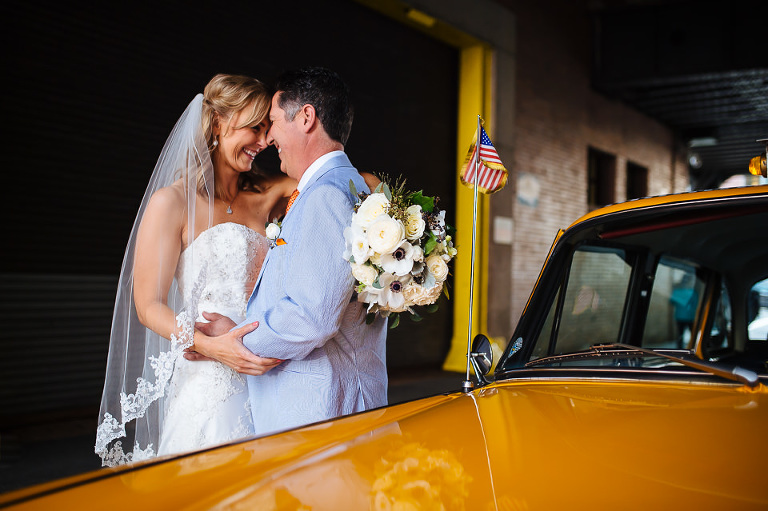 Bride and groom embrace behind the vintage Checker cab