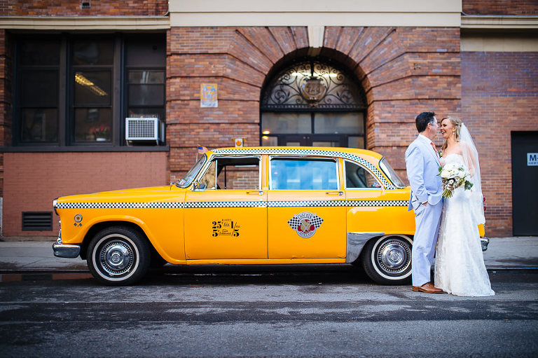Portrait of bride and groom with their vintage Checker cab