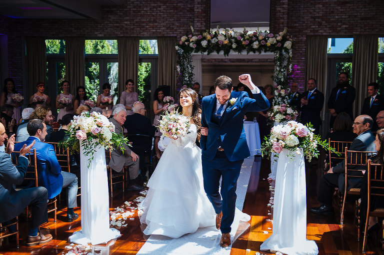 Groom fist pumps as he walks the bride out of the ceremony
