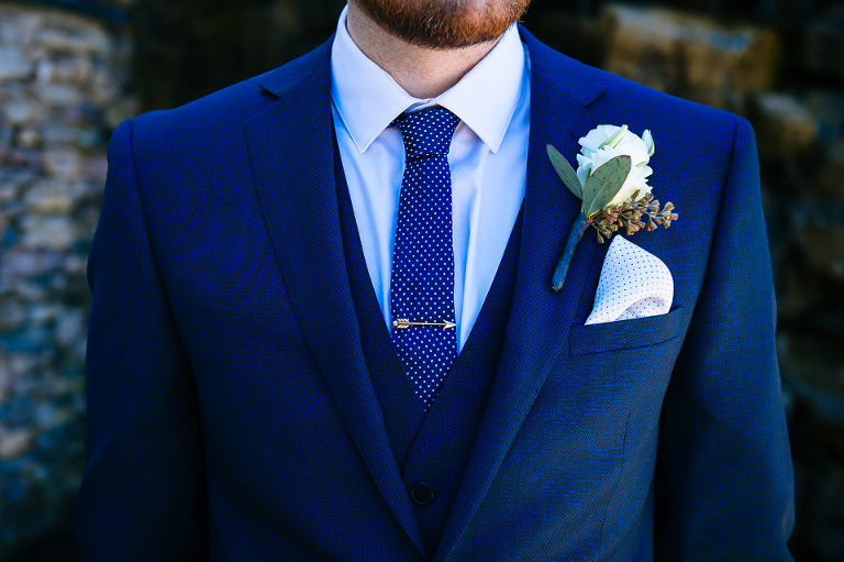 Detail of groom's suit, tie, tie bar, pocket square, and boutonniere