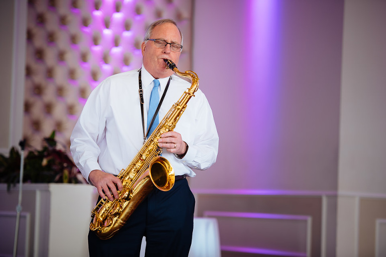 Father of the groom playing the saxophone during the reception