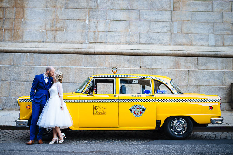 Portrait of wedding couple next to Checker cab