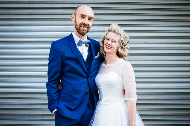 Wedding couple in front of industrial doors