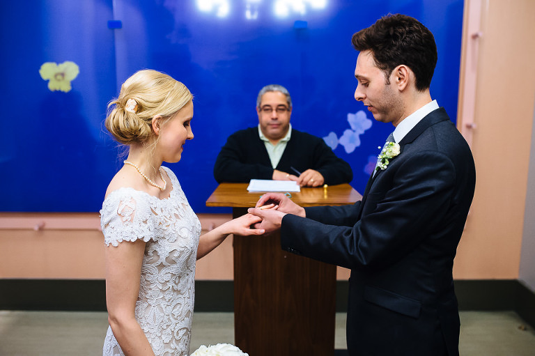 Groom places ring on bride's finger during ceremony