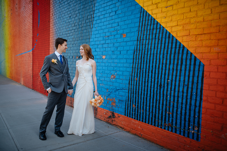 Bride and groom in front of graffiti in DUMBO