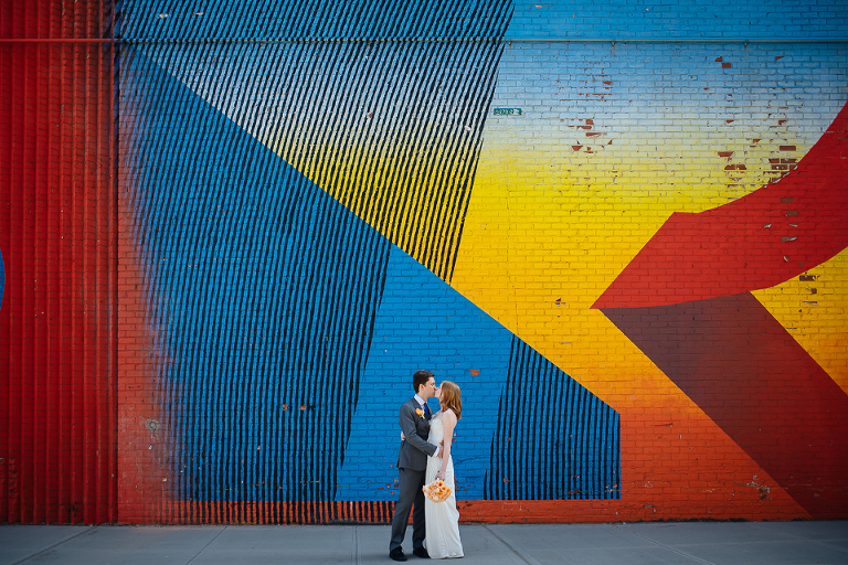 Bride and groom kissing in front of Brooklyn graffiti