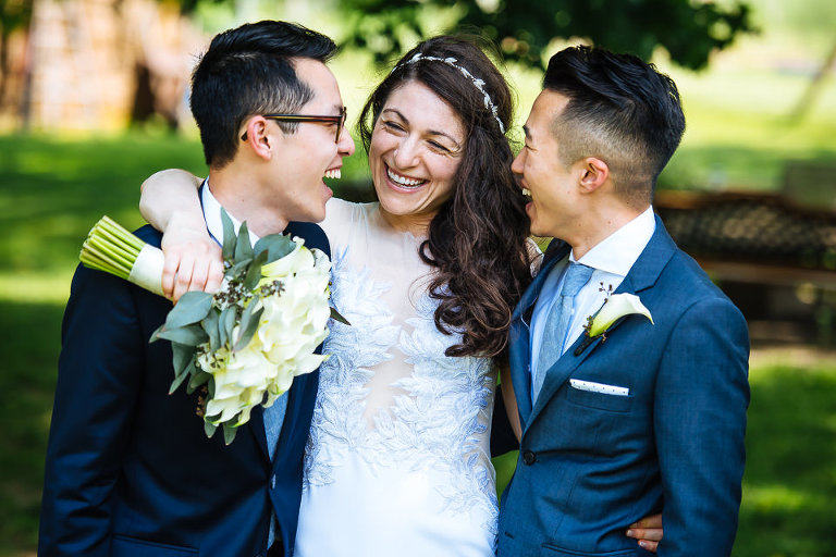 Bride laughing with her two brothers