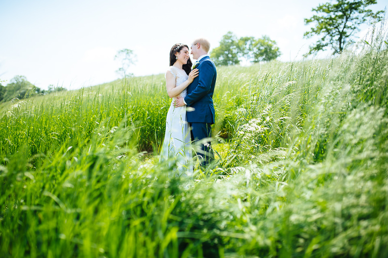 Wedding couple embracing in a field