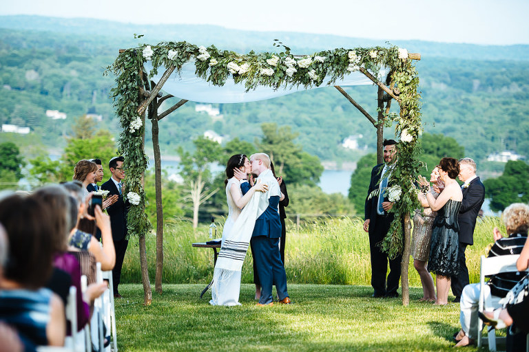 Groom kisses the bride at their hilltop ceremony