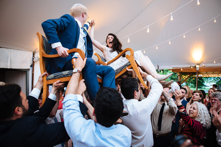 Wedding couple being lifted in chairs during the horrah