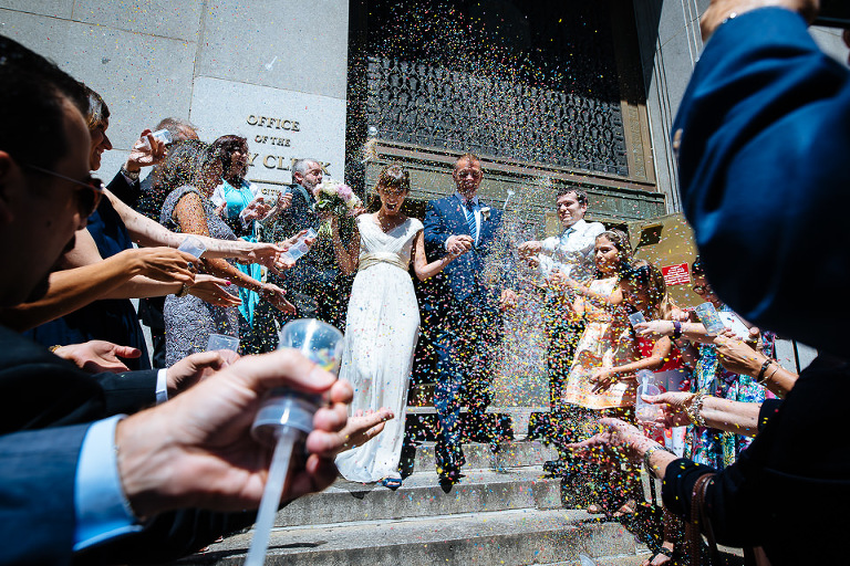 Bride and groom exit City Hall with confetti