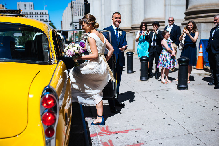 Bride and groom getting into their Checker cab