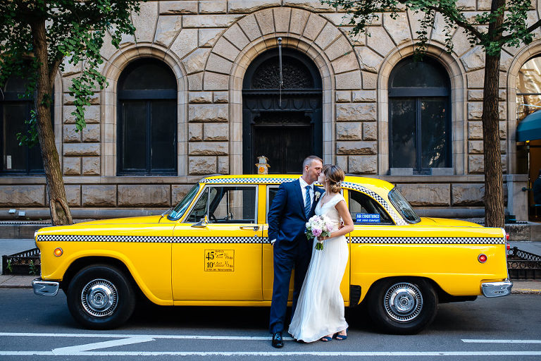 NYC elopement photographer, bride and groom with their rented Checker cab