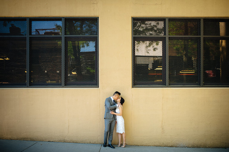 Wedding couple kissing in alley