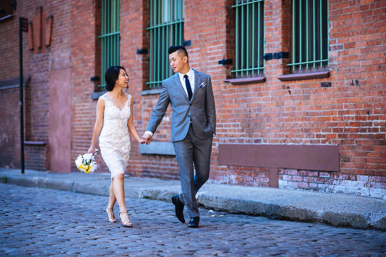 Bride and groom strolling down cobblestone street