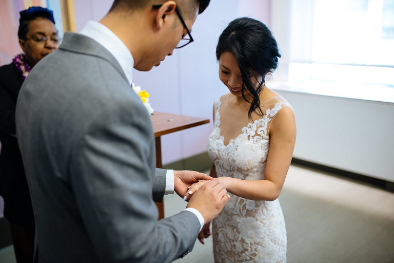 Groom slipping ring onto bride's finger