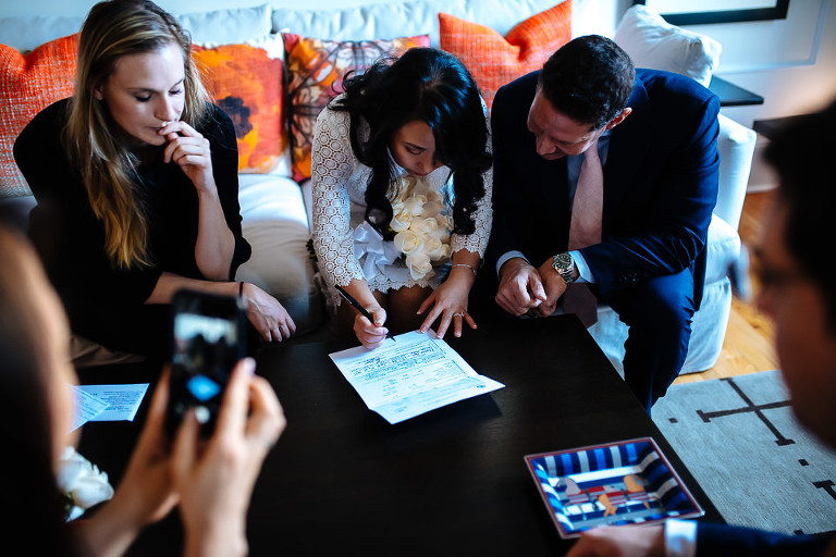 Wedding couple signing license in their apartment