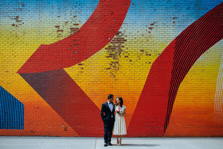 Bride and groom with graffiti wall