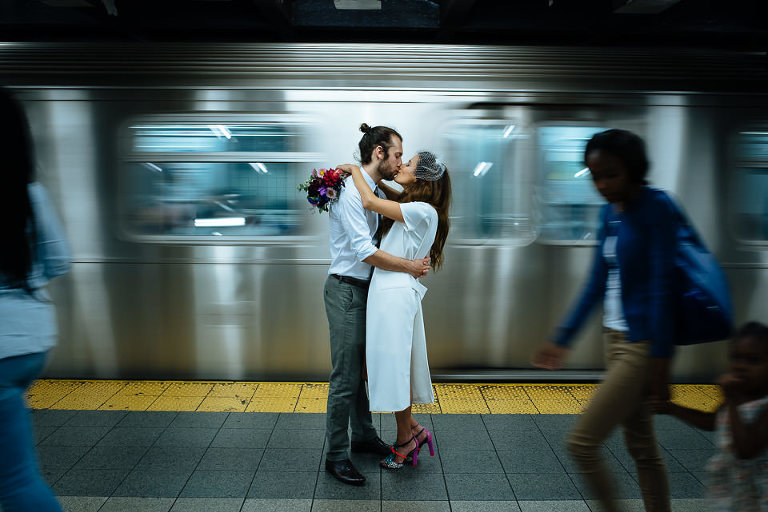 Bride and groom kissing on the subway platform