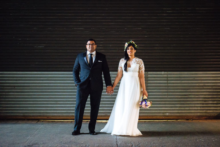 Bride and groom in front of industrial door