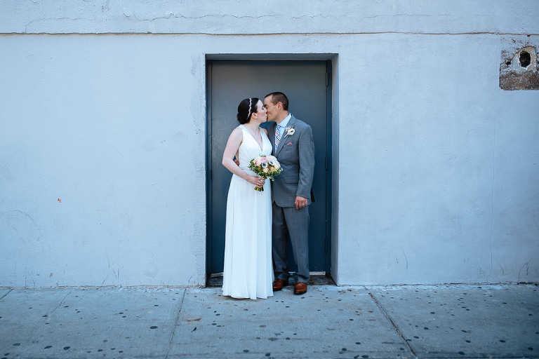The wedding couple kiss on a NYC sidewalk
