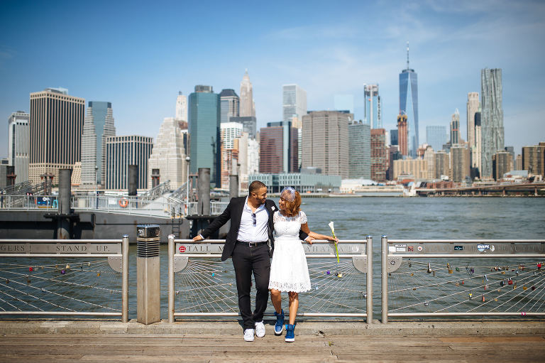The wedding couple basking in the morning sun with the NYC skyline in the background