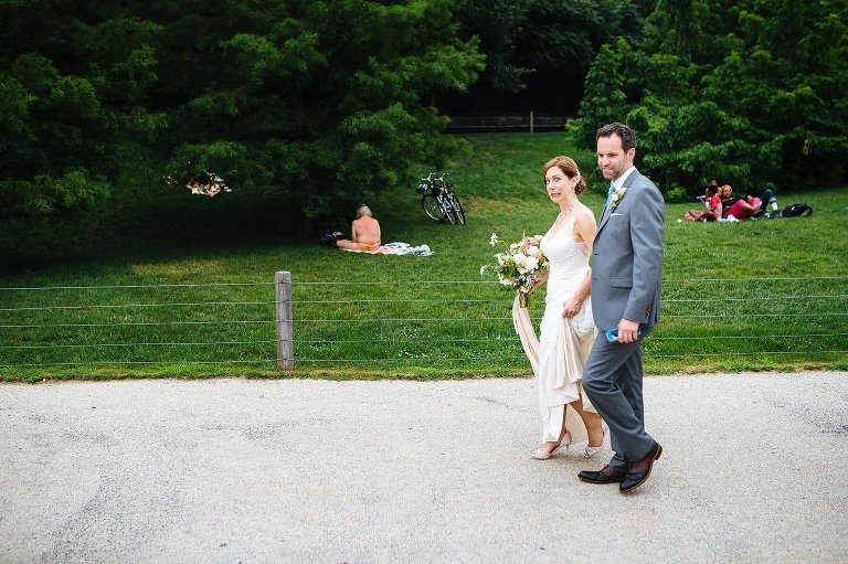 Bride and groom walk past a guy in a thong in Brooklyn Bridge Park