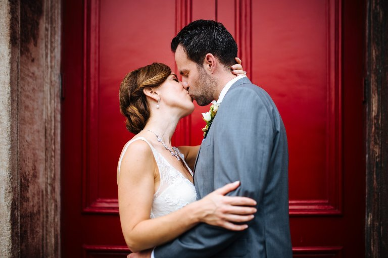 Finding a pop of color for their wedding portraits with a brilliant red door