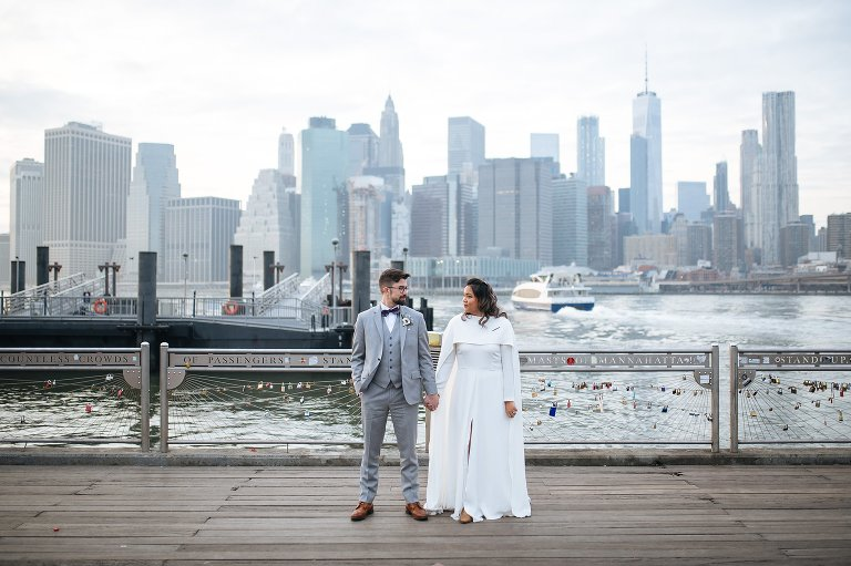Wedding couple with the skyline views from Fulton Ferry Landing in DUMBO Brooklyn