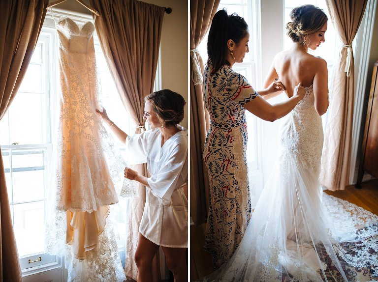 Bride admiring her wedding dress and her friend helping her get ready
