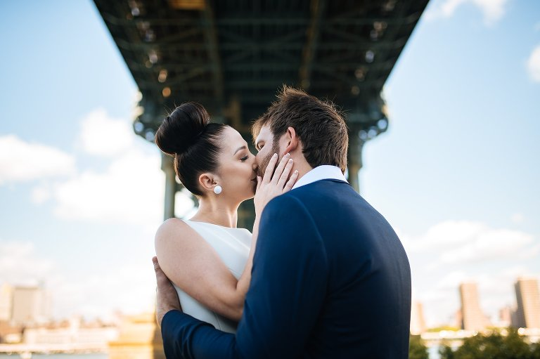 Bride and groom kissing in DUMBO
