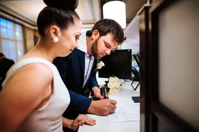 Signing the marriage license paperwork at City Hall wedding