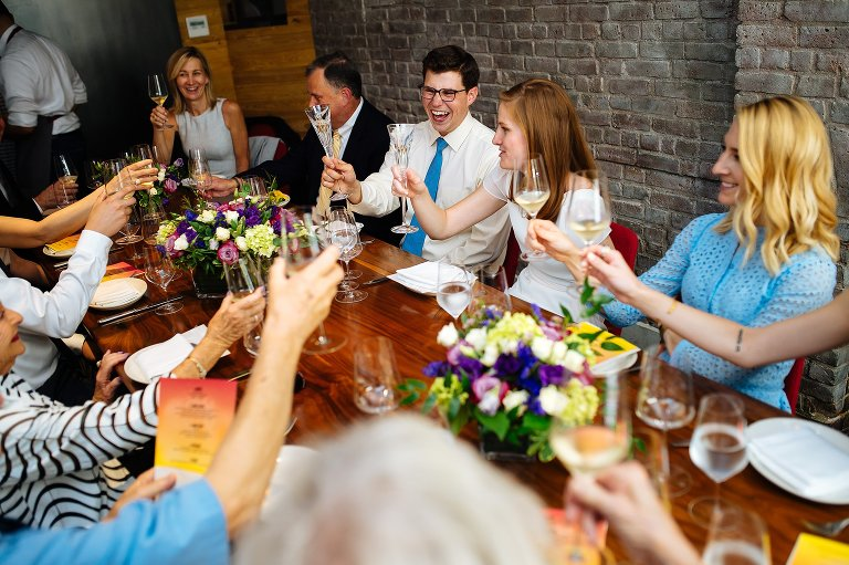 Wedding couple and guests toast in the private dining room at Charlie Bird in NYC