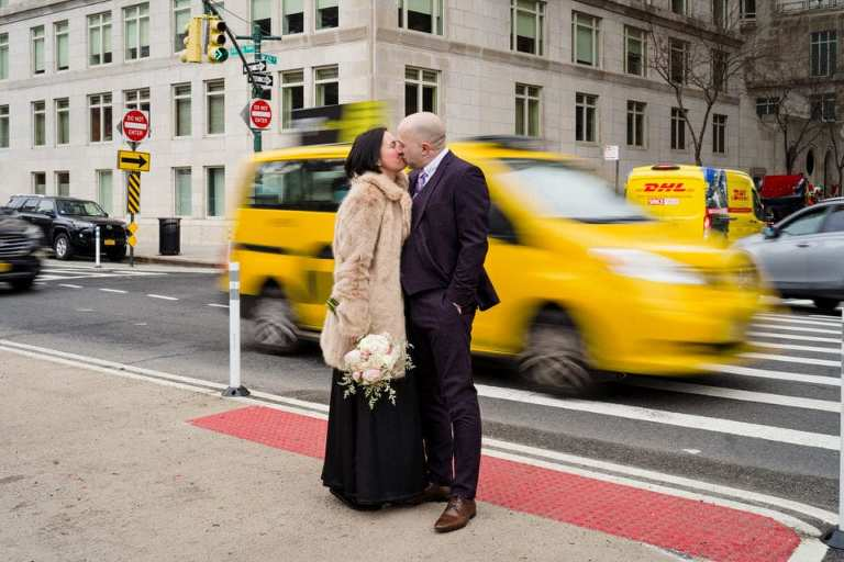 Taxi cab passing behind a wedding couple outside Central Park.